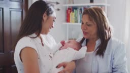 Young Hispanic mother holding her baby son with grandmother looking on, waist up, close up