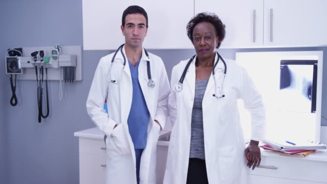 young hispanic radiologist standing beside senior doctor inside clinic - scientific imaging technique stock videos & royalty-free footage