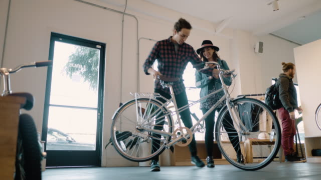 a young hispanic woman and her boyfriend consider buying a beautiful new city bike - hipster culture stock videos & royalty-free footage