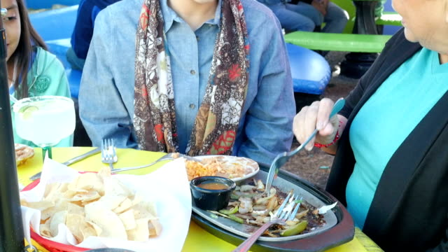 young hispanic woman having meal with grandmother outdoors on restaurant patio - mexican restaurant stock videos & royalty-free footage