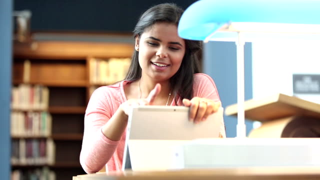 vídeos y material grabado en eventos de stock de mujer joven hispana en biblioteca con tableta digital - mano en la barbilla
