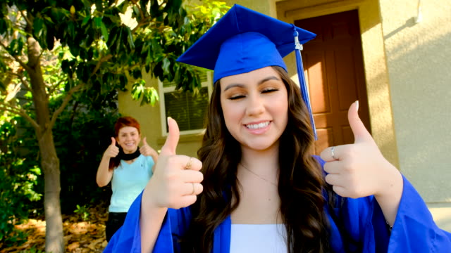 young hispanic woman posing celebrating her graduation with her mother in the background - spanish and portuguese ethnicity stock videos & royalty-free footage