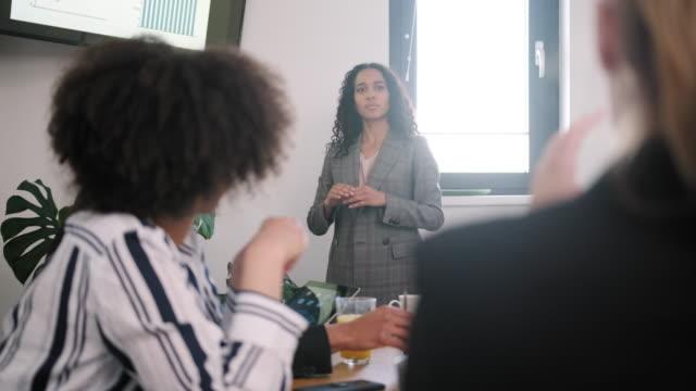 giovane donna ispanica che presenta un brief di presentazione ai colleghi - strategia di vendita video stock e b–roll