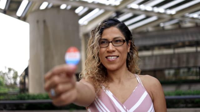 vidéos et rushes de jeune femme hispanique avec j'ai voté autocollant - urne électorale