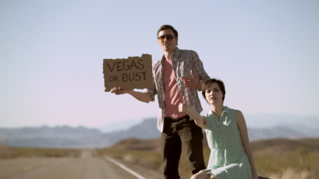 Young hitchhikers thumb a ride from a passing minivan on a lonely desert road, run to catch up