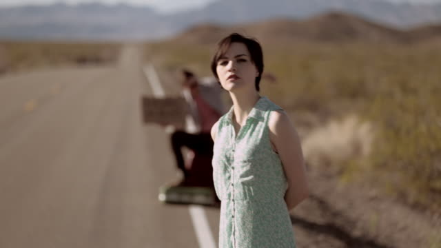 Young hitchhikers wait by the side of a lonely desert road