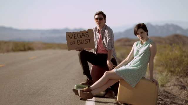 Young hitchhikers with a Vegas Or Bust sign wait by the side of a lonely desert road