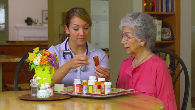ms young home health care worker helping older women with her medication, austin, texas, usa - 老化点の映像素材/bロール