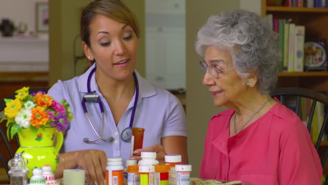 MS Young home health care worker helping older women with her medication, Austin, Texas, USA