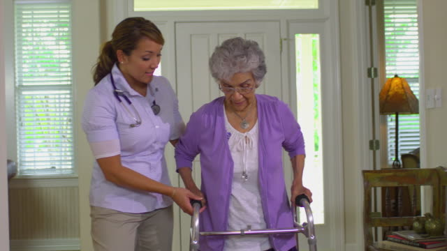 MS SHAKY Young home health care worker helping older women with her walker, Austin, Texas, USA