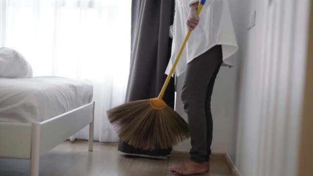 young housewife cleaning spotless floor with brush and dustpan, great hygiene - stock video - sweeping stock videos & royalty-free footage