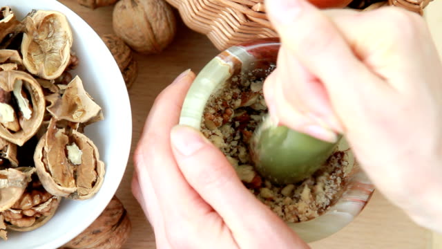 young housewife grinds walnuts in a mortar - walnut stock videos & royalty-free footage