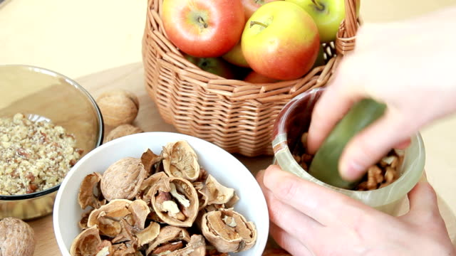 young housewife grinds walnuts in  mortar - nutshell stock videos & royalty-free footage