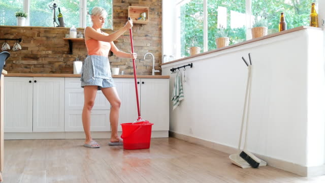 Young housewife mopping house floors