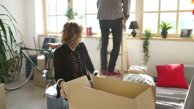 vídeos y material grabado en eventos de stock de joven marido y mujer desempacando en apartamento nuevo - reforma