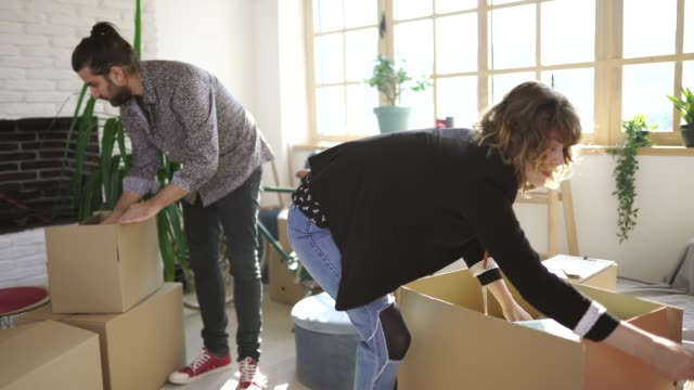 young husband and wife unpacking new home - young couple stock videos & royalty-free footage