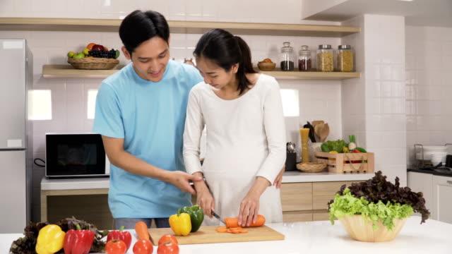 若い夫は台所で健康食品を準備するためのニンジンをチョッピング妊娠中の妻を助けに来る - 談笑する点の映像素材/bロール