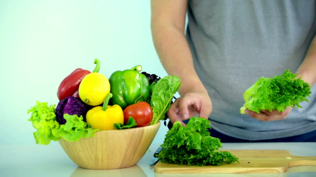 Young husband prepare salad for wife