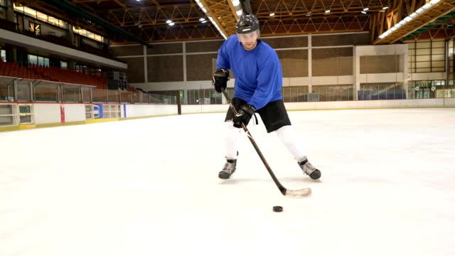 若いアイス ホッケー プレーヤーへの取り組みと目標でスポーツ アリーナでトレーニング中に撮影します。 - アイスホッケー点の映像素材/bロール