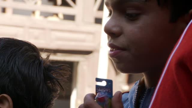 vídeos de stock, filmes e b-roll de young indian boy holding a toothbrush in its packaging. - boca humana