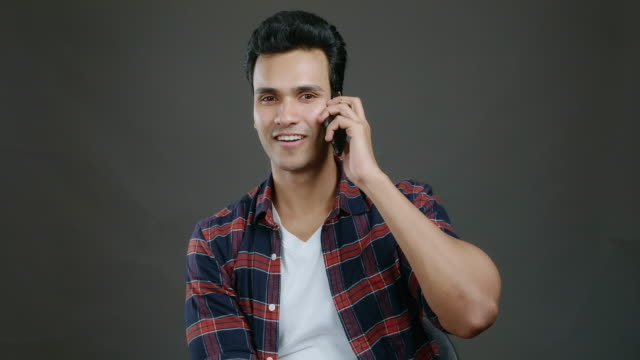 young indian hipster talking on mobile phone,isolated in grey background. indian man in casual cloth. medium shot. - attitude stock videos & royalty-free footage