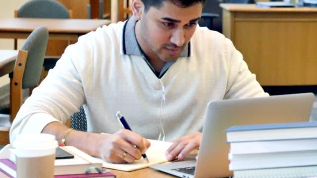 vídeos de stock, filmes e b-roll de estudos de estudante jovem colégio masculino indiano na biblioteca do campus - aluno mais velho