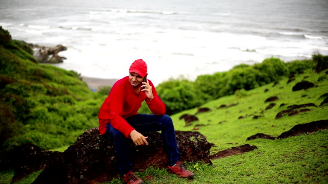 Young Indian man talking on mobile Phone near seashore