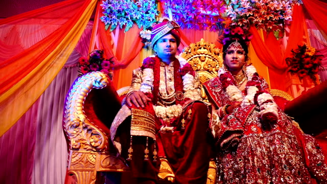 young indian wedding couple sitting on luxury sofa on wedding stage - married stock videos & royalty-free footage