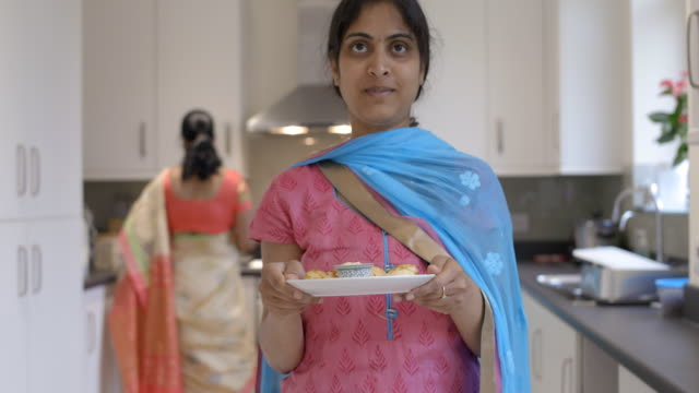 Young Indian woman holding plate of Indian snacks to camera