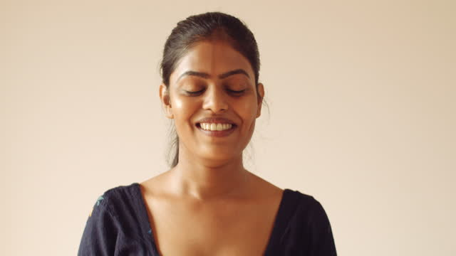 young indian woman looks at camera pov smiles a toothy grin laughs and has a good mood with happy joyous and positive vibes - studio shot stock videos & royalty-free footage