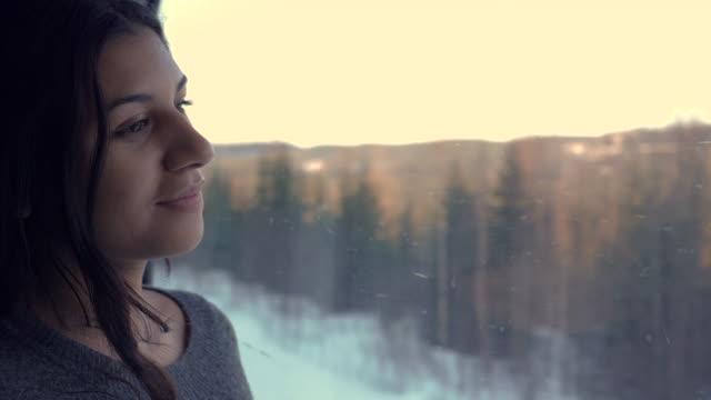stockvideo's en b-roll-footage met jonge indische vrouw die zich in nachttrein aan abisko bevindt die uit het venster op sneeuwlandschap kijkt - train vehicle
