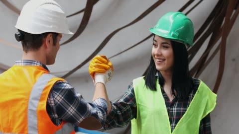 vídeos y material grabado en eventos de stock de los empleados jóvenes de la industria agitan las manos después de un trabajo exitoso - casco herramientas profesionales