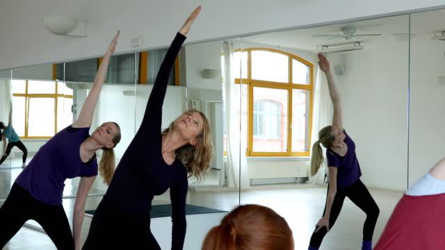 Young instructor teaching women in yoga class