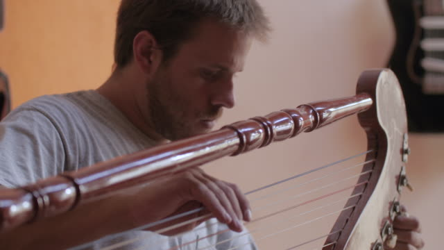 young instrument maker tuning a harp at studio - guitar stock videos & royalty-free footage