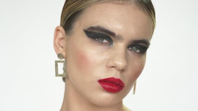 vídeos de stock e filmes b-roll de a young intense woman with geometric eyeshadow - fotografia da cabeça