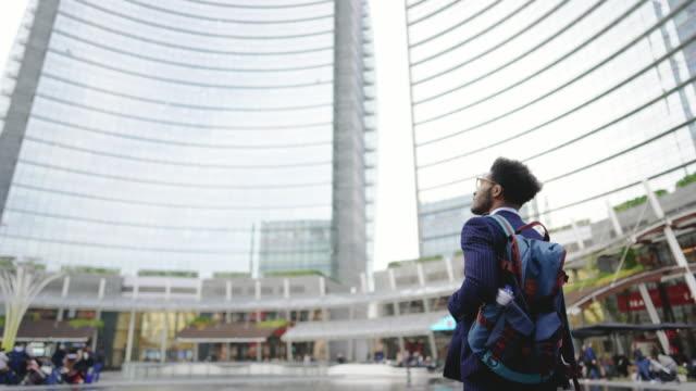 junger praktikant beim blick auf sein neues bürogebäude - chance stock-videos und b-roll-filmmaterial