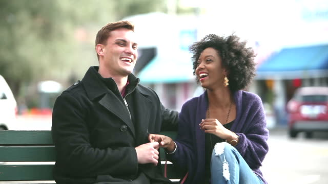 Young interracial couple in city run up and sit on bench