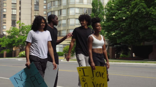 Young interracial group makes protest signs