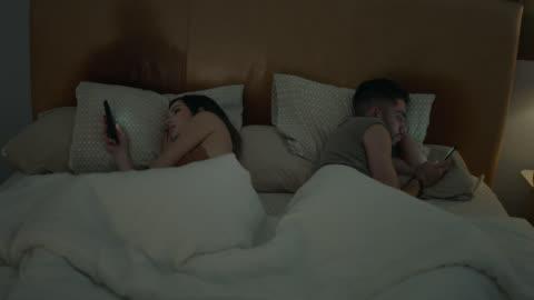 young interracial millennial couple sharing a bed face away from each other and stare at smartphones instead. - dålig vana bildbanksvideor och videomaterial från bakom kulisserna