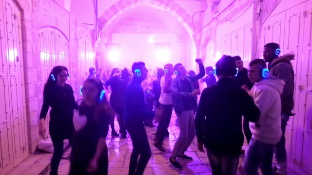 vídeos y material grabado en eventos de stock de young israelis and palestinians dancing together in a silent disco wi-fi headphone party at the roofed alley of souk al khawajat market in the muslim... - auriculares equipo de música