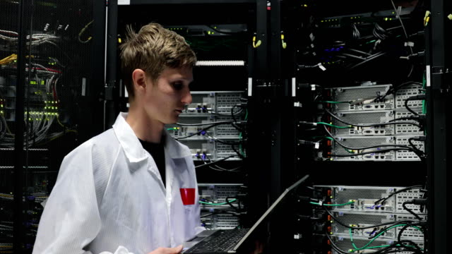 young it technician walking into server room - upgrade stock videos and b-roll footage