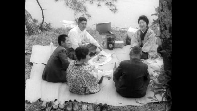 young japanese adults celebrate at cherry blossom festival; 1962 - cross legged stock videos & royalty-free footage