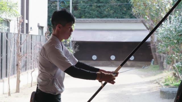 vidéos et rushes de jeune archer japonais pratiquant le sport traditionnel de kyudo - terme sportif