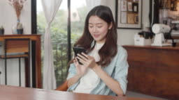 Young Japanese Asian girl using smartphone checking social media on the internet on the table at coffee shop.