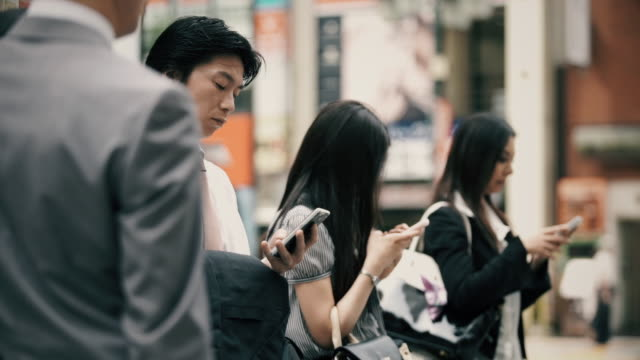 Young Japanese Businesspeople Looking at Phones