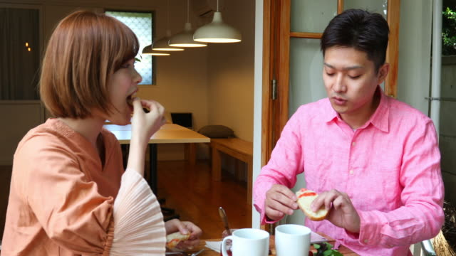 一緒に朝食を楽しむ若い日本人カップル - 朝食点の映像素材/bロール