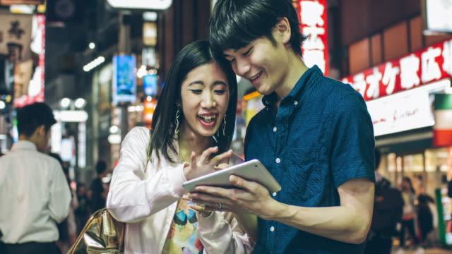 若い日本人夫婦楽しむデジタルタブレットを - 喜び点の映像素材/bロール