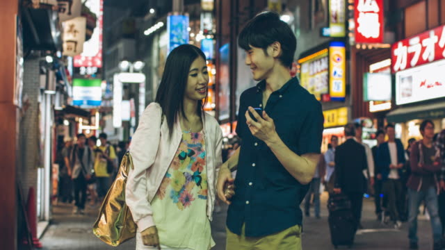 Young Japanese couple looking for an address at mobile phone