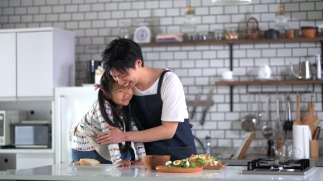お父さんが昼食を作っているのを見る若い日本人娘 - daughter点の映像素材/bロール