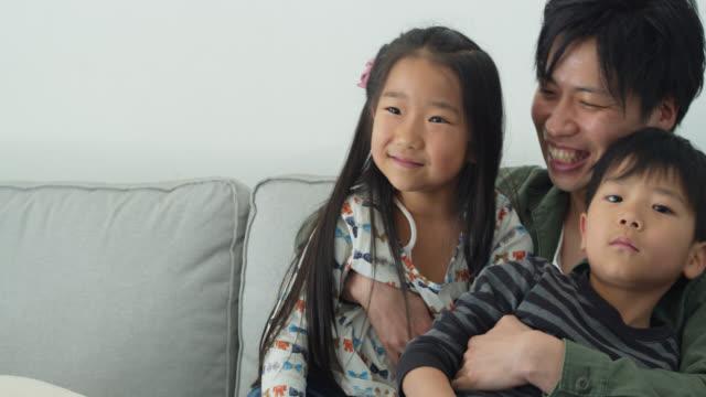 家庭で子供を抱きしめる若い日本人の父 - 団らん点の映像素材/bロール